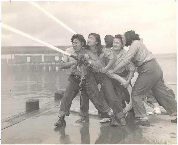 mujeres sosteniendo una manguera de bomberos apagando un incendio