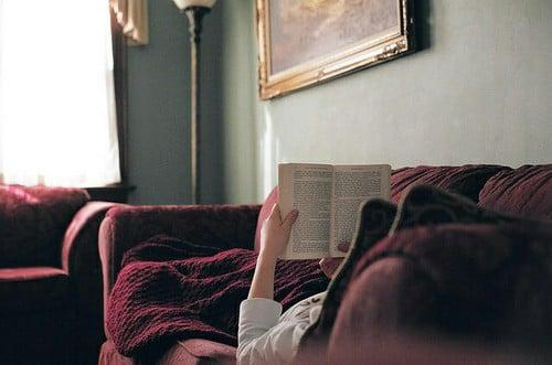 chica acostada en un sofá leyendo un libro