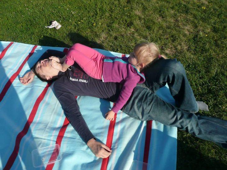 niña dormida sobre las piernas de su padre en un jardín