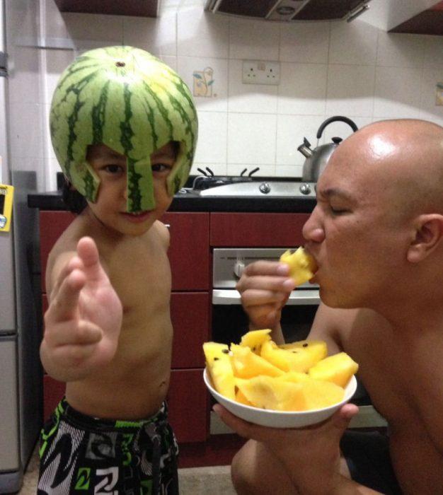 niño con una sandia como casco y padre comiéndose el resto de la fruta en un plato
