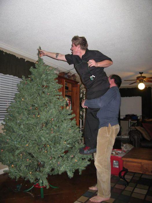 hombre cargando a otro para que coloque una estrella en la punta de un árbol de navidad