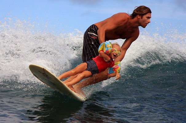 hombre sosteniendo a una niña en una tabla de surfear mientras están en el agua del mar