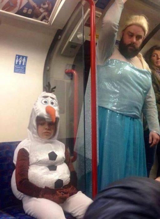 hombre vestido de princesa de disney acompañando a su hija vestida de hombre de nieve