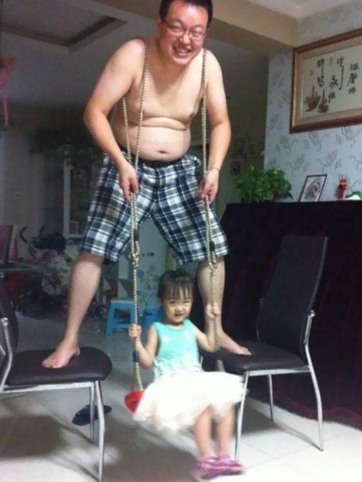 hombre con lazos en sus brazos y arriba de dos sillas columpiando a su hija