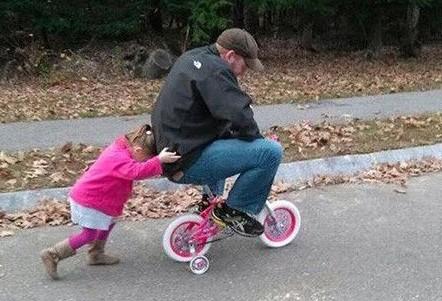niña empujando a su padre que esta montado en una bicicleta