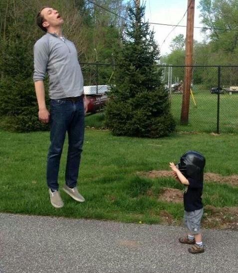hombre parado en el pasto mientras su hijo esta frete a él