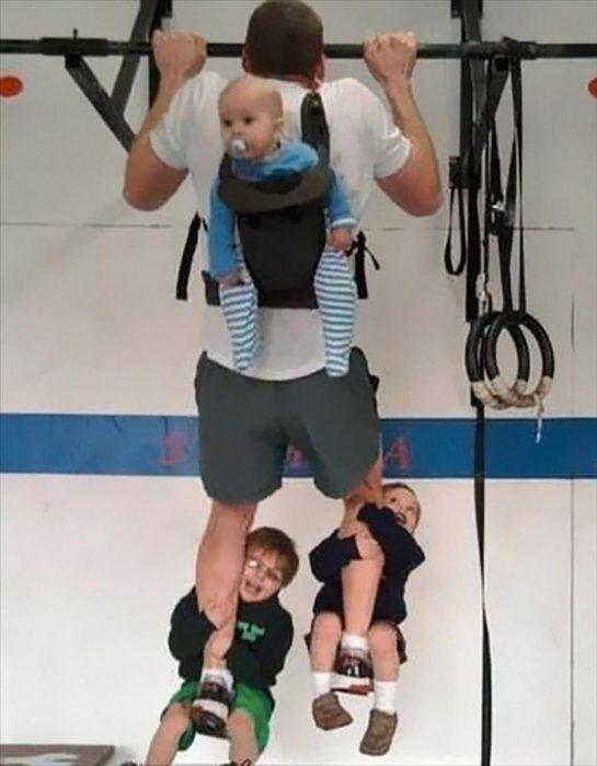 padre haciendo pesas con sus hijos