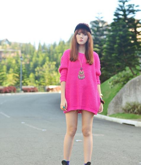 mujer usando un suéter largo parada en medio de la carretera