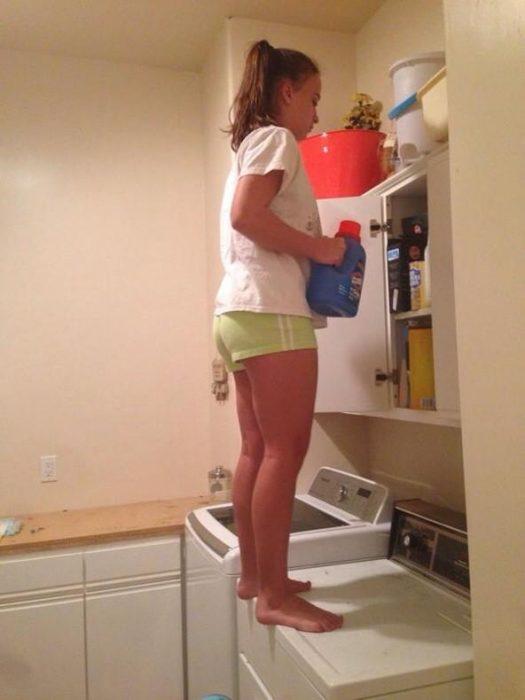 mujer bajita sobre una lavadora