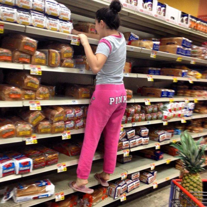 mujer escalando los estantes del supermercado