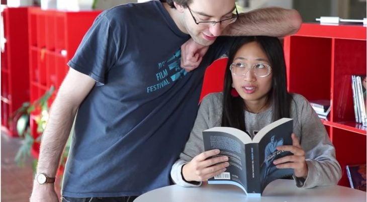 mujer sentada leyendo un libro y hombre recargando su brazo en la cabeza de ella