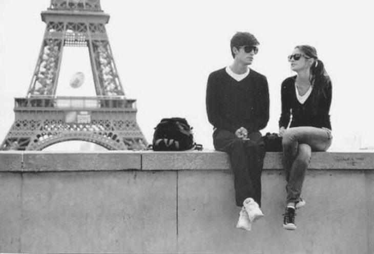 pareja platicando con la torre de paris de fondo