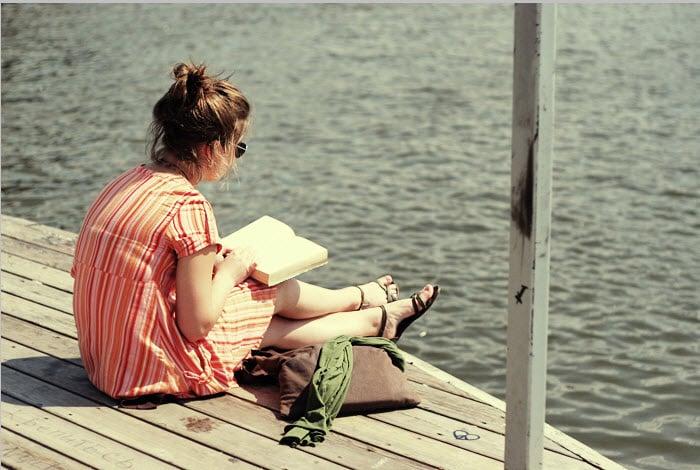 mujer sentada en un muelle leyendo un libro