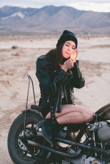 mujer sobre una motocicleta fumando