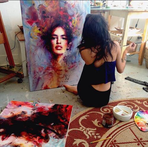 mujer sentada en el suelo pintando