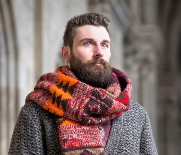 hombre con barba usando una bufanda y un suéter gris
