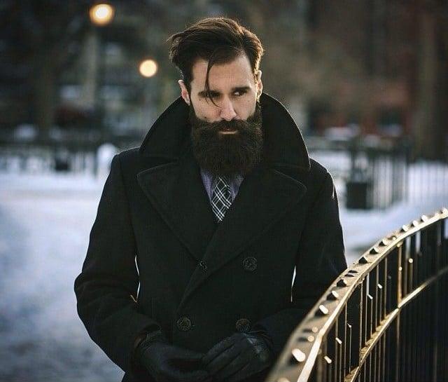 hombre con barba usando un saco parado a un lado de un puente