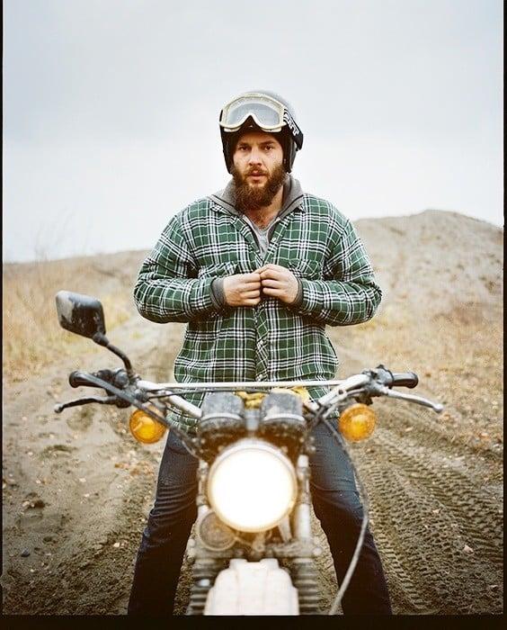 hombre con barba usando una chamarra verde en una motocicleta