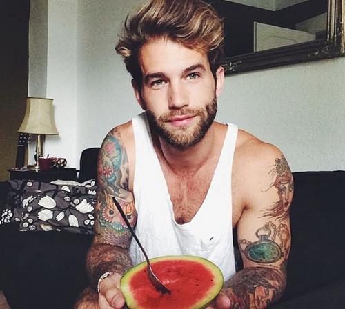 hombre rubio tatuado sentado comiendo sandia