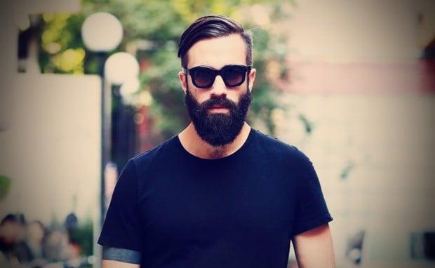 hombre con barba usando una camisa negra caminando por la calle