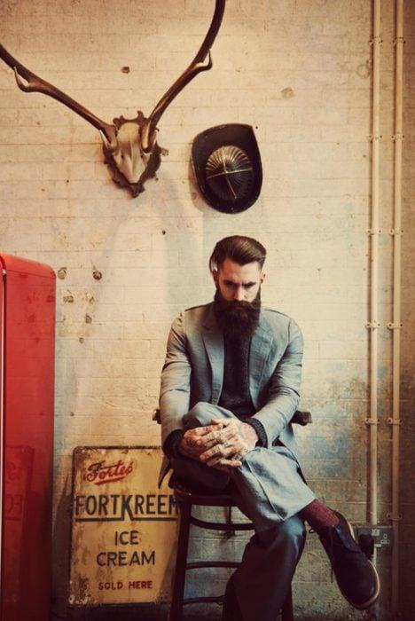 hombre con barba sentado en una silla