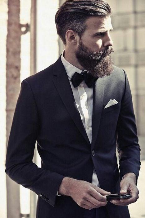 hombre con barba usando un traje y parado en medio de la calle