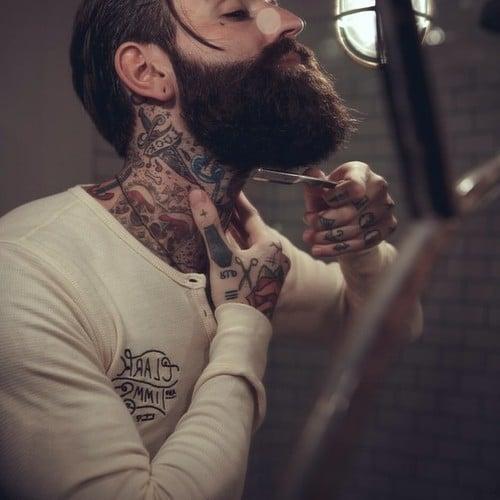 hombre tatuado con barba rasurándose frente al espejo