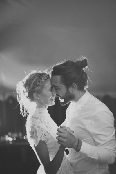 pareja vestida de novios bailando y sonriendo