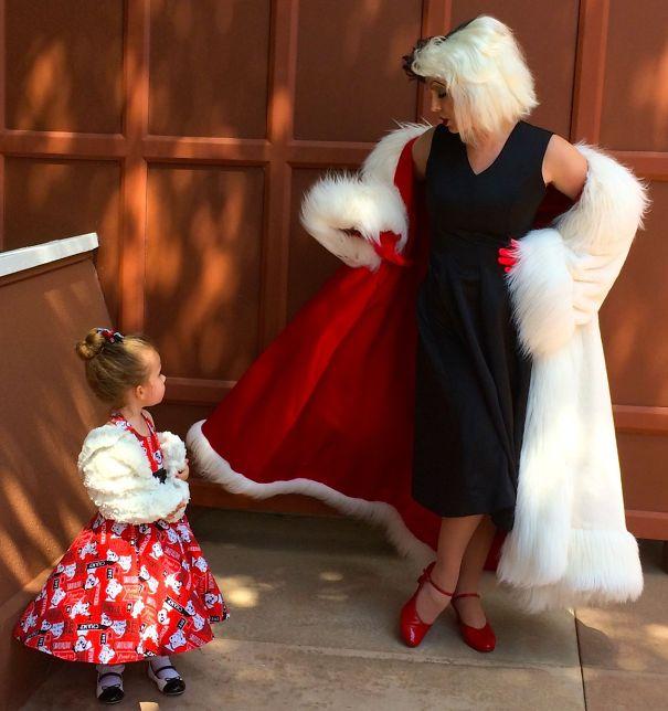 niña mirando a una mujer con vestido negro y abrigo blanco