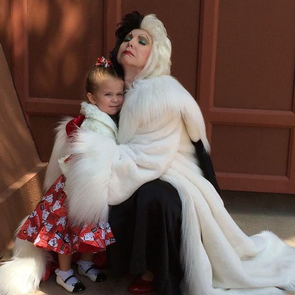 mujer abrazando a una niña y cubriéndola con su abrigo en medio de la calle