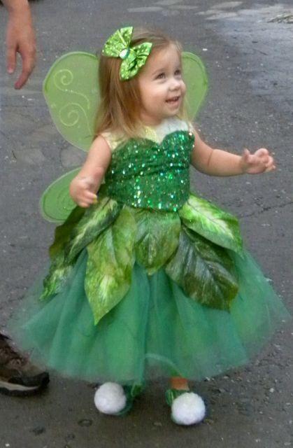 niña vestida de campanita parada en medio de un parque de diversiones