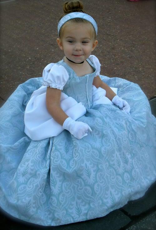 niña con un vestido de la cenicienta en un parque