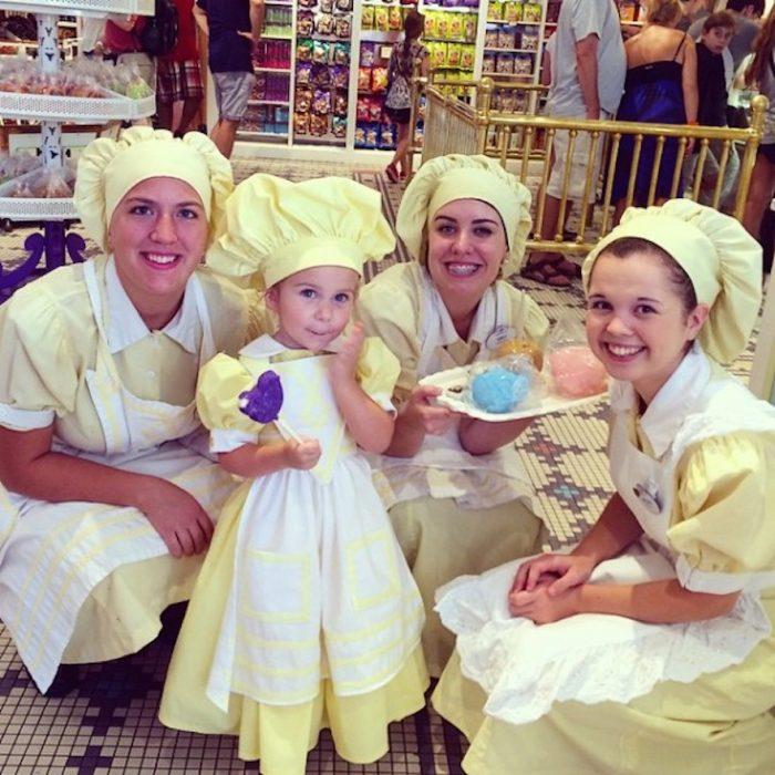 mujeres y niña vestidas de cocineras sosteniendo una charola de pan