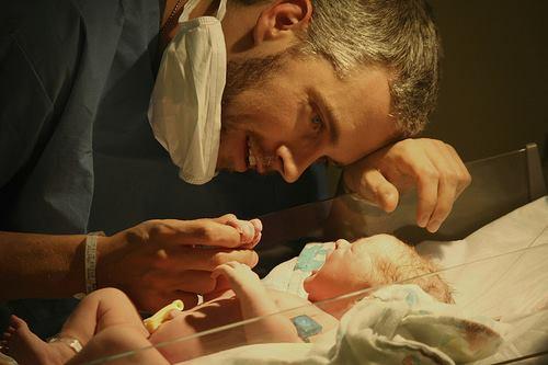 papá viendo a su bebé en su cunero con tapabocas