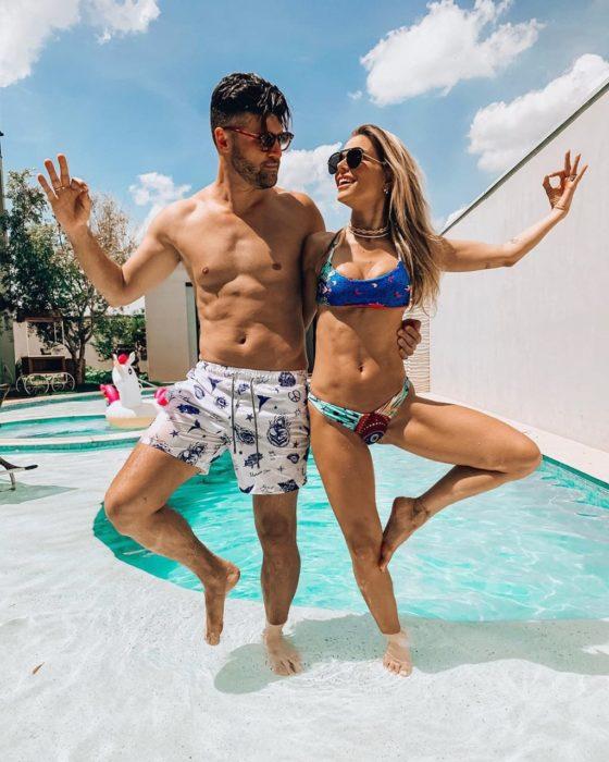 pareja haciendo pose de yoga frente a una alberca