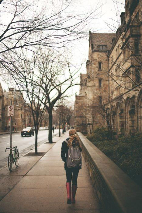Chica caminando por la calle con una mochila