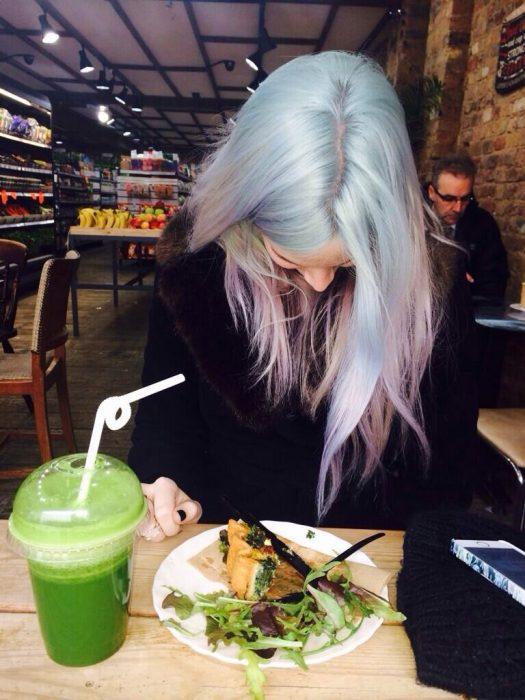 chica de cabello plateado comiendo comida vegetariana