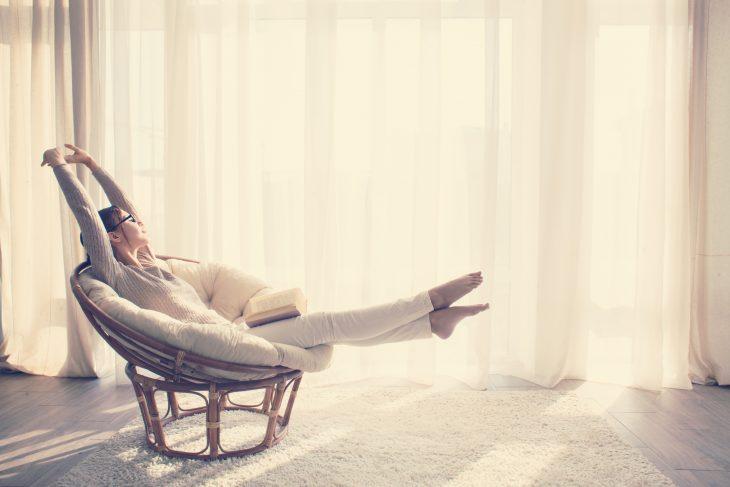Chica sentada en un sofá al lado de una ventana leyendo