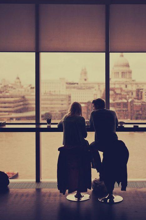 Personas sentadas frente a un ventanal platicando