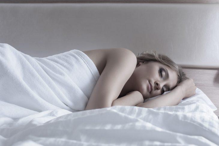 Chica dormida con sabanas blancas