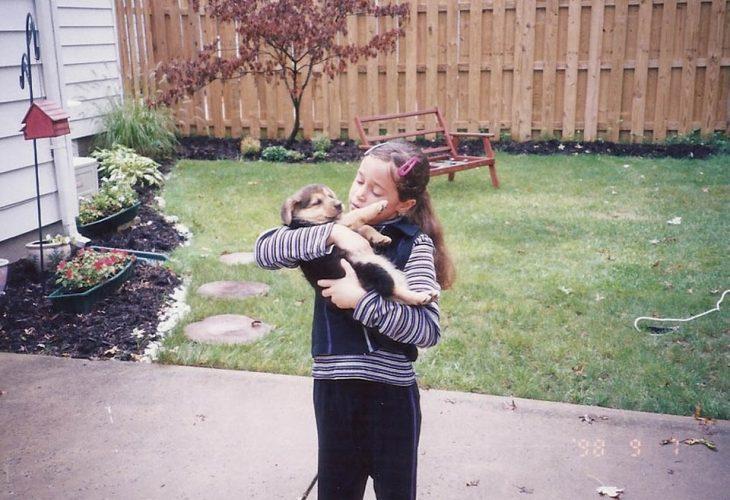 Niña cargando un perro pequeño