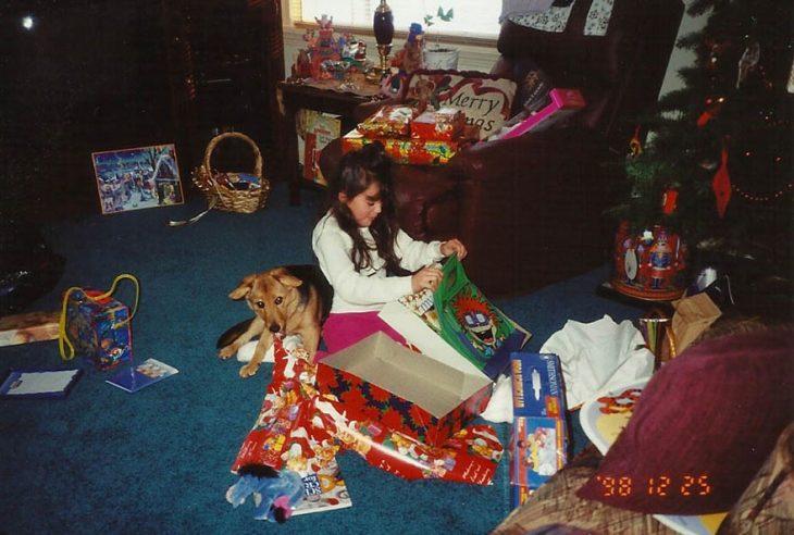 Niña abriendo regalos de navidad con un perro a su lado
