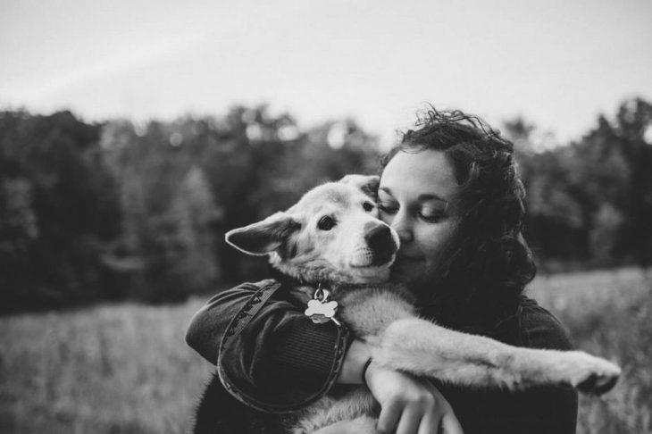 Foto en blanco y negro de un perro y su dueña abrazados