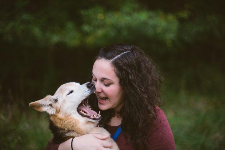 Mujer con un perro mientras bosteza
