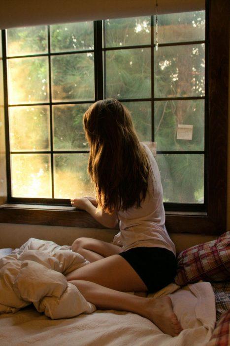 Chica sentada en su cama mientras observa por la ventana