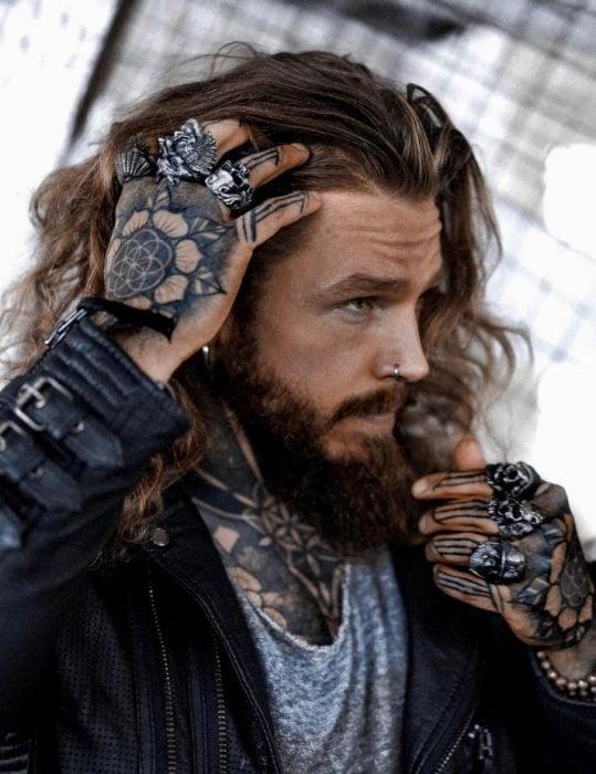 Hombre de cabello largo, barba y tatuajes en las manos