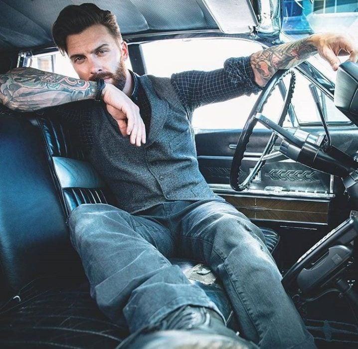 Hombre tatuado y con barba sentado en un carro