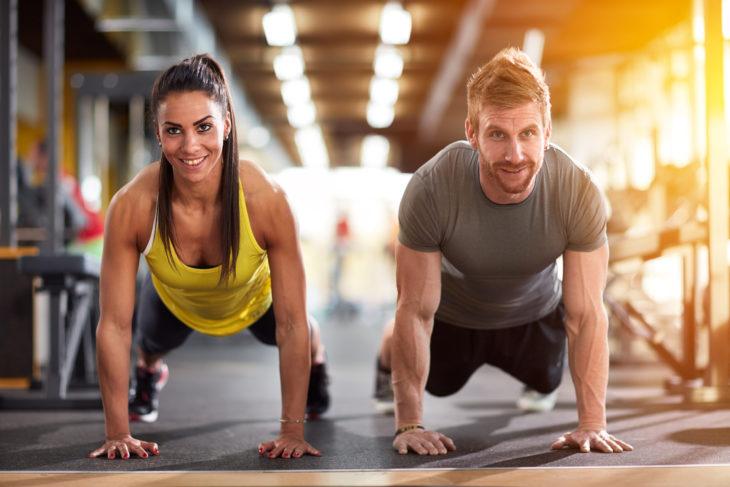 Pareja de novios haciendo ejercicio en las maquinas de un gimnasio