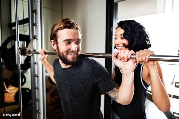 Chico levantando pesas con la ayuda de su novio