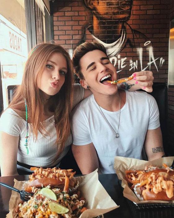 Pareja de novios en un restaurante comiendo papas fritas y pizza